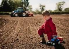 child playing with a toy tractor