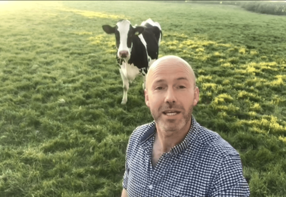 farmer in field with cow