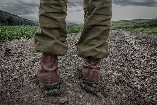 person standing in army trousers and boots looking out to field