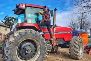 female farmer washing red tractor